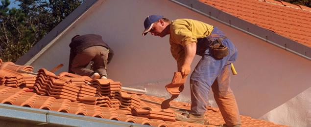 Hombres reparando el techo de una casa